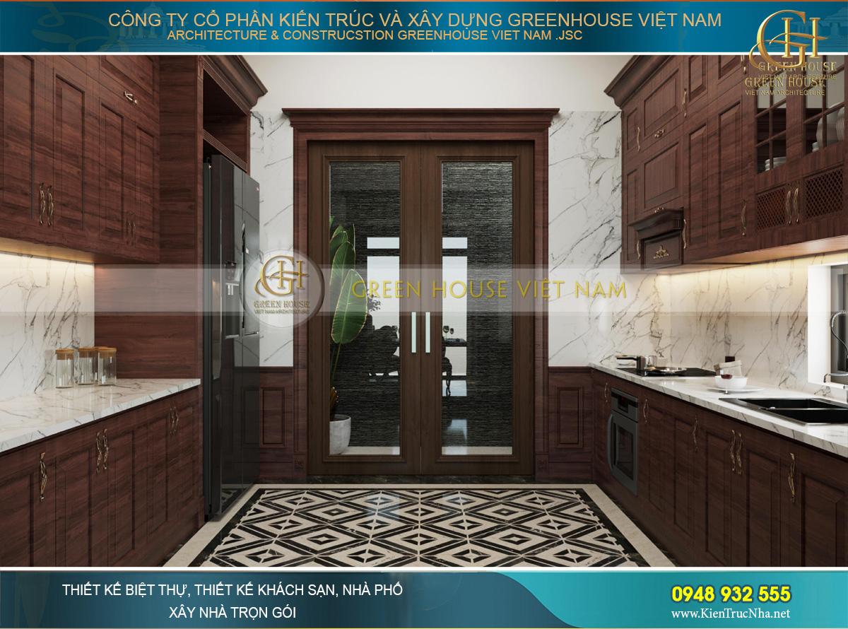 Phía trong là không gian phòng bếp với chất liệu gỗ tự nhiên và đá granite vân mây sáng bóng